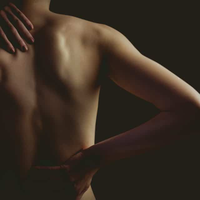 woman with a back injury on black background