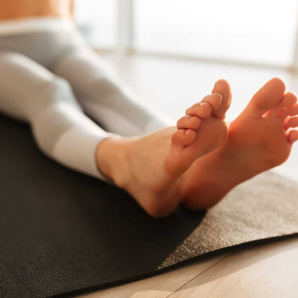 Female feet on yoga mat at home