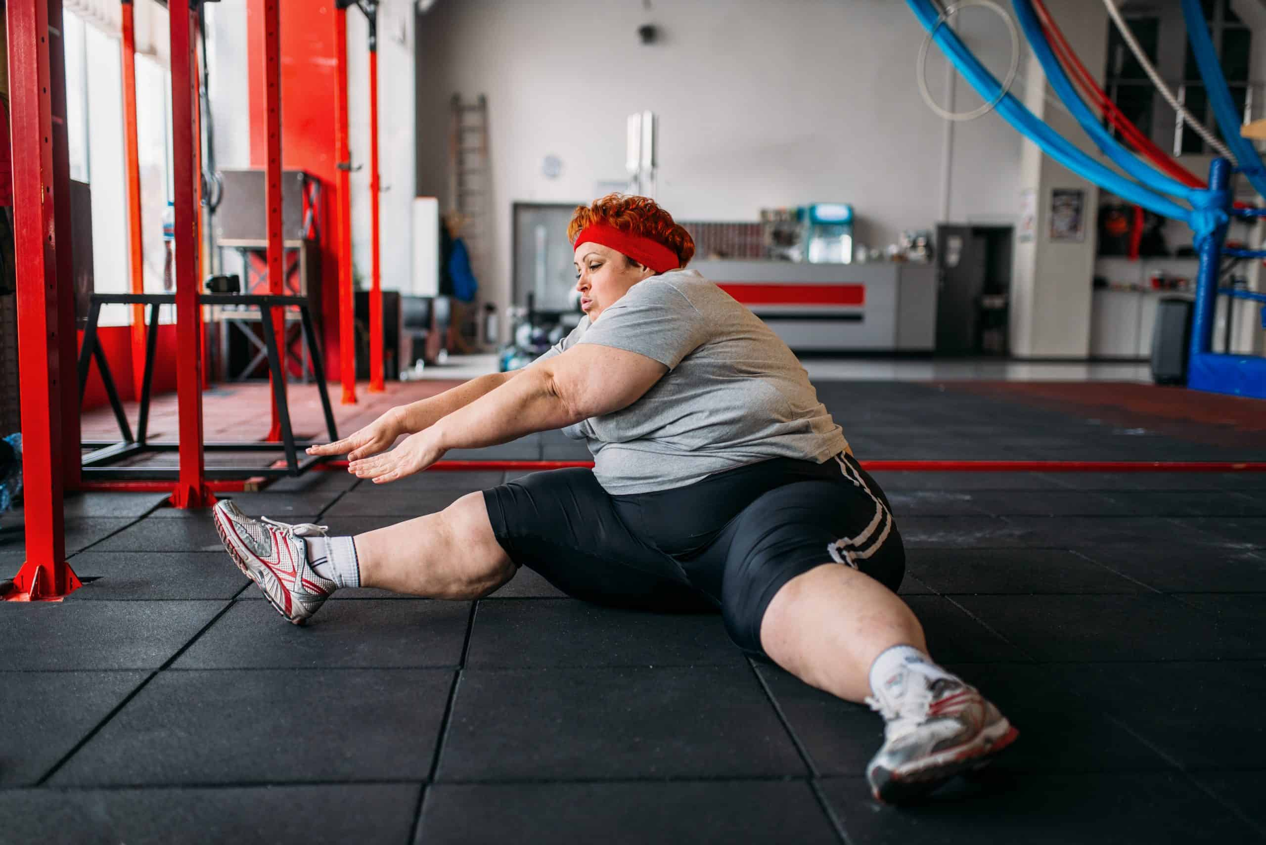 an obese woman works out in the gym
