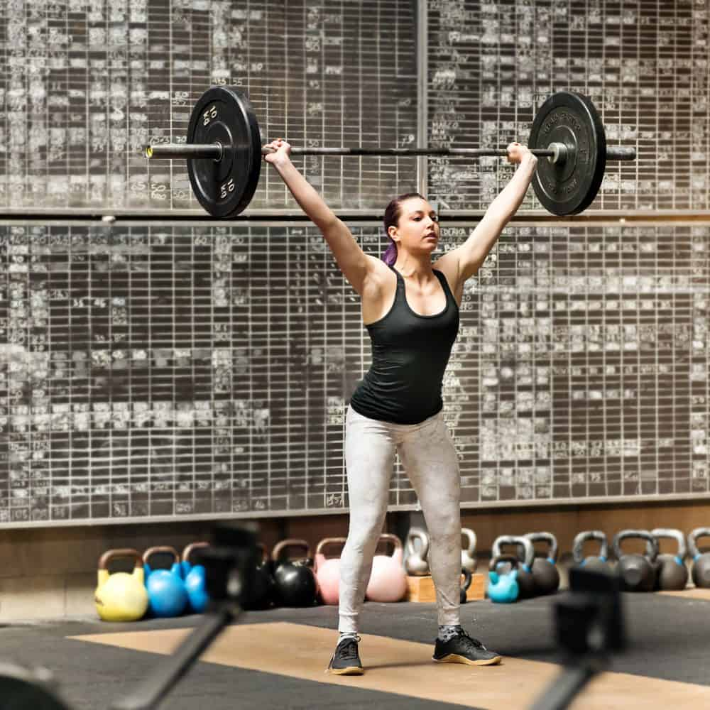 Young athletic woman doing the snatch in a gym