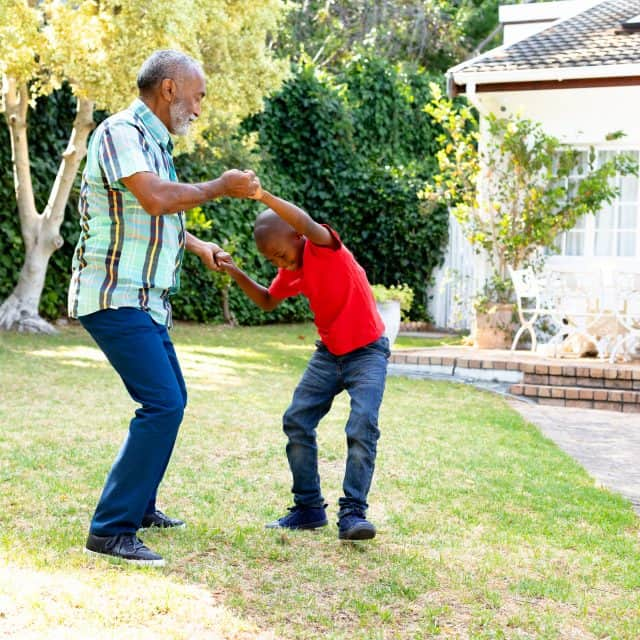Senior man spending time with his grandson in their garden on a sunny day, teaching him dancing on the lawn.