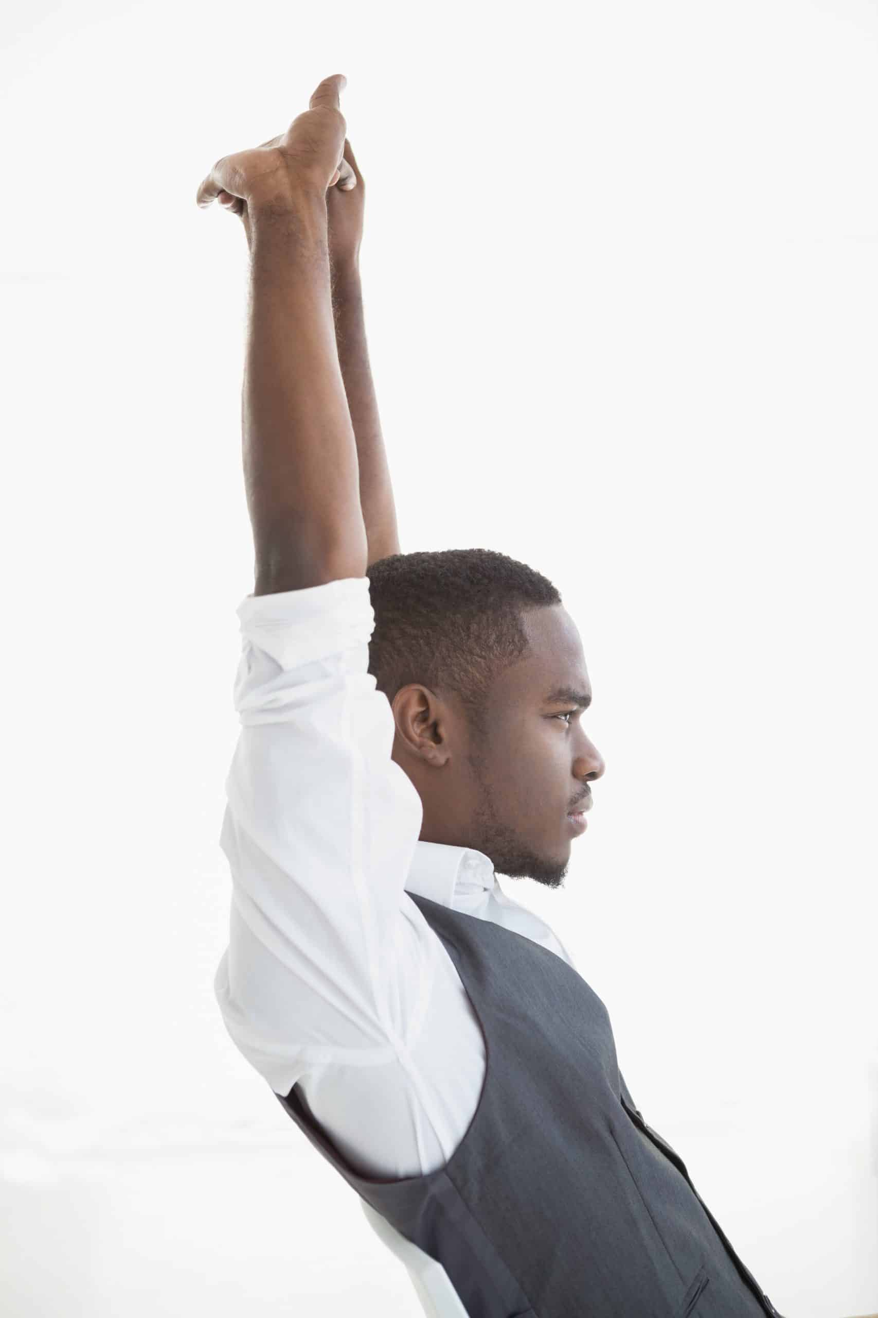Smiling businessman stretching his arms in his office